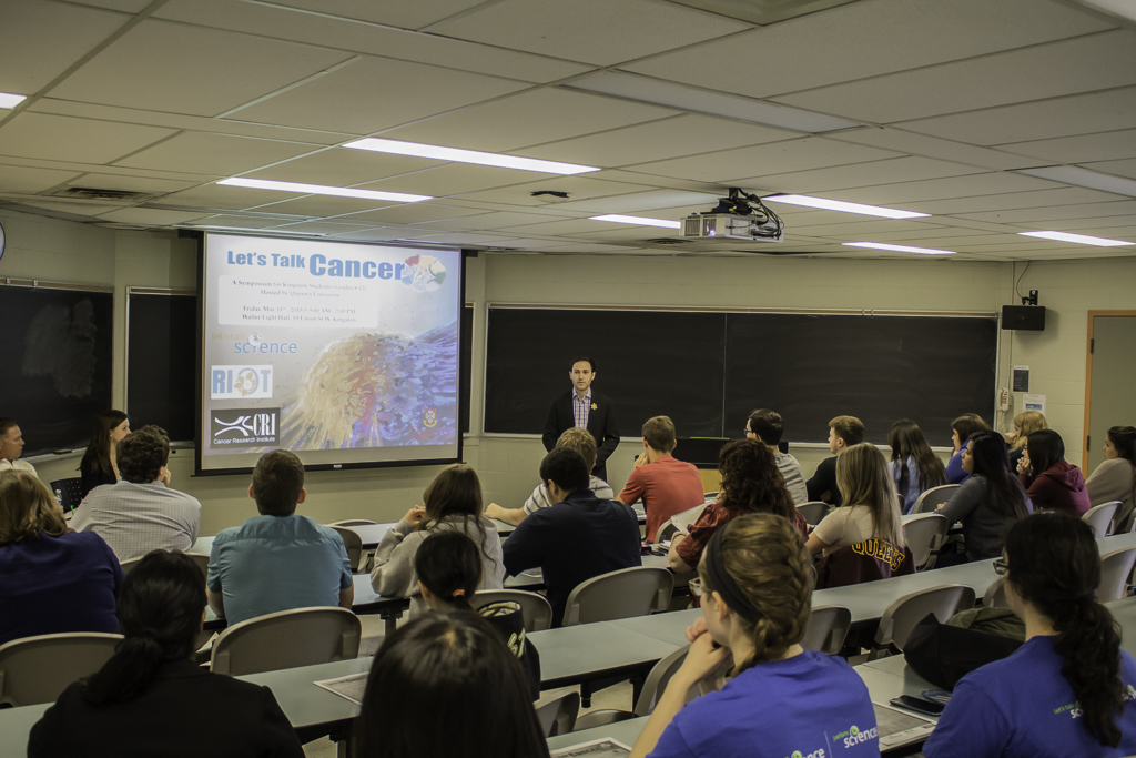 Researcher presenting to group of youth on cancer research