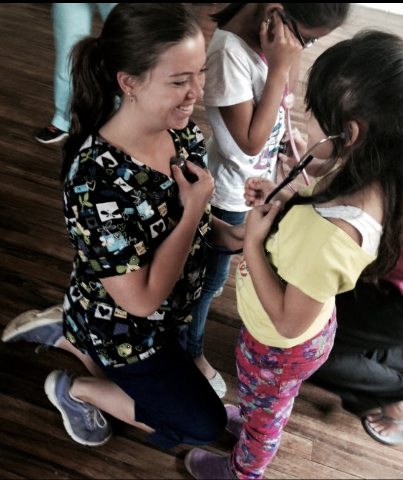 Erica Dupuis showing child how to use stethoscope