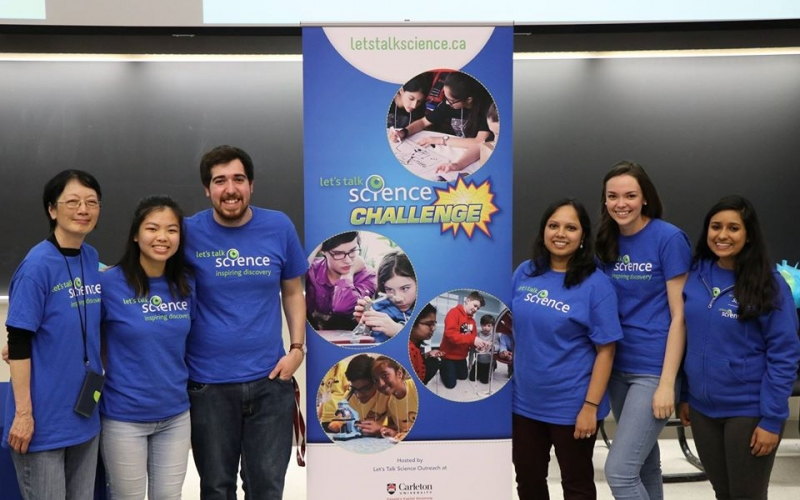 Anjulia Wong standing with fellow volunteers in front of Let's Talk Science Challenge banner.