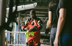 Marine Police Officer suits up in a scuba diving drysuit