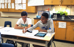 Two students work on an assignment in their science classroom with a piece of chart paper and a tablet.