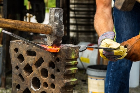 Blacksmith hammering a red hot piece of metal