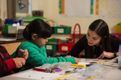 Female teacher working on a hands-on activity with magnets with two students in a classroom.