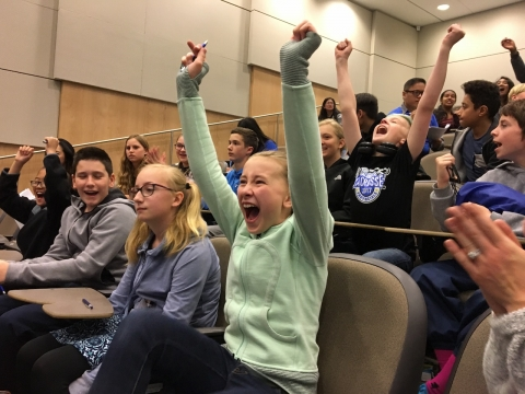 Students with arms raised, cheering at Let's Talk Science Challenge quiz competition.