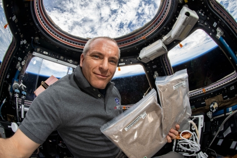 Canadian Astronaut David Saint-Jacques holds up Tomatosphere seeds while aboard the International Space Station, Earth is in the background