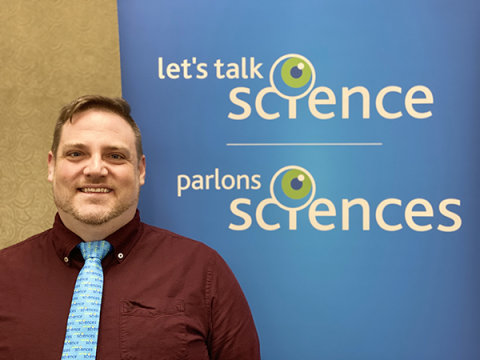 A photo of Greg Ryerson in front of a Let's Talk Science banner