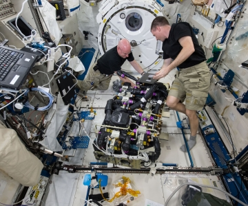 Scott Kelly et Terry Virts inspectent le système d'élimination du dioxyde de carbone de la SSI (Photo via Wikimedia Commons)