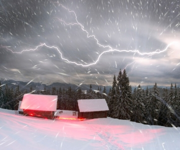 Thundersnow near a cabin on a hillside