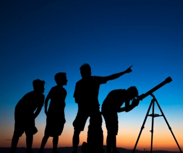 Adult and children looking through telescope
