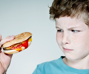 a boy looks at a hamburger