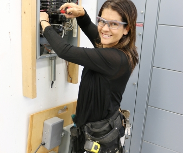 Julie-Claire Hamilton working at electrical breaker box