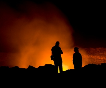 Volcanologists looking at glowing lava