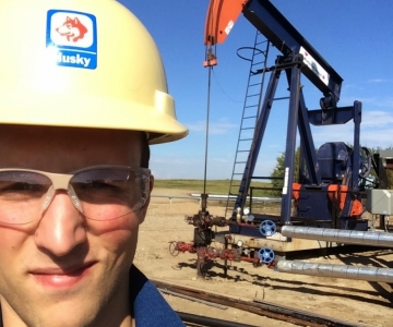 Adam Tofani in front of a pump-jack