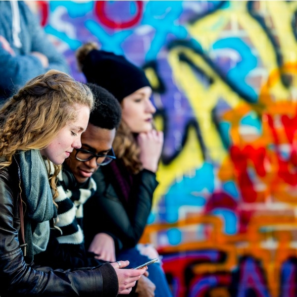 Teens near a graffiti wall