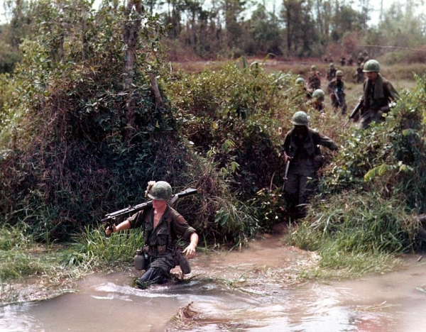 American troops wading across a flooded stream in 1968, during the Vietnam War