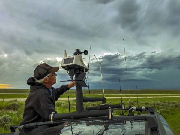 A storm chaser adjusts the rooftop weather station