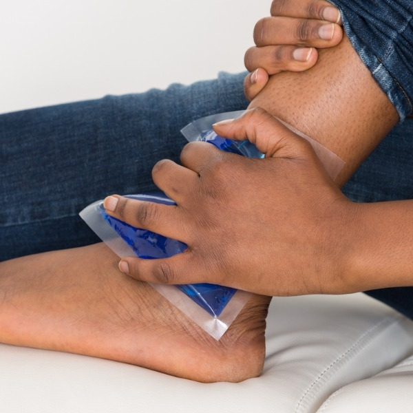 A person's hand holding a cold pack on an ankle