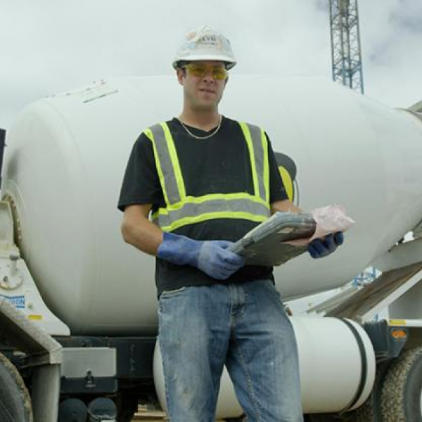 Geotechnical engineer stands with a clipboard in front of a construction site wearing safety gear.
