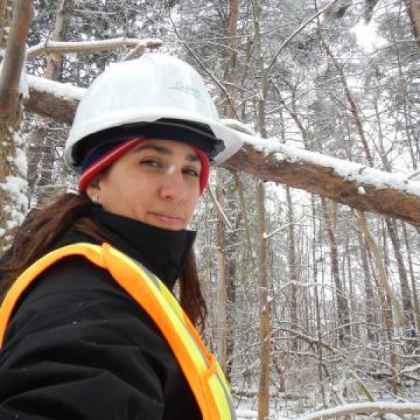 Urban Forestry Technologist stands in front of a snowy forest in a hard hat and high visibility vest.