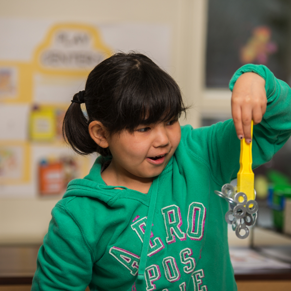 Child in awe while learning through play using magnetic force to pick up washers at a Let's Talk Science Outreach event